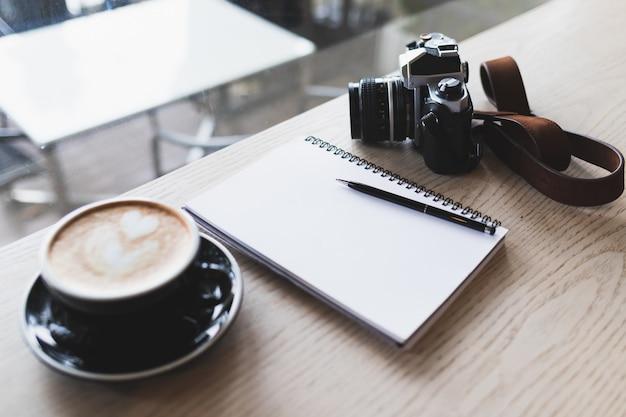 Notizbuch, weinlesekamera und heißer cappuccino platziert auf eine braune hölzerne tabelle in einer kaffeestube