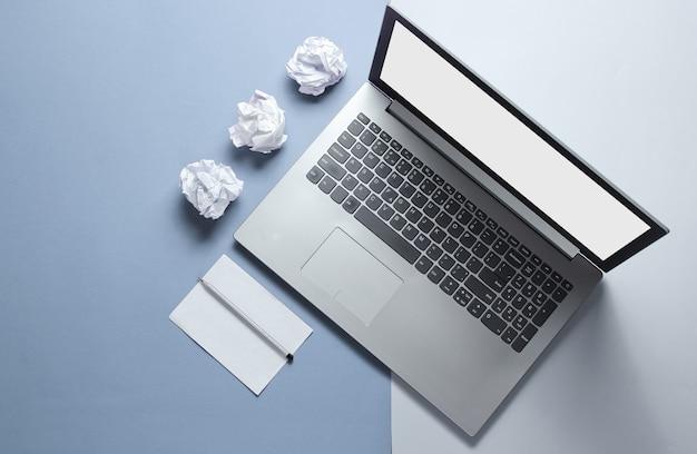 Notizbuch, zerknitterte papierkugeln, blatt papier mit einem bleistift auf grauem blau.