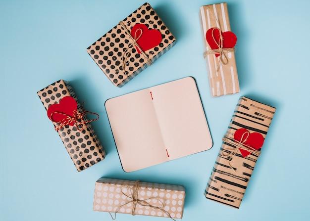 Notizbuch zwischen geschenken in den sweetiepapieren mit dekorativen herzen