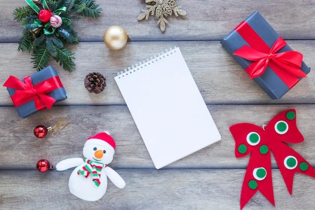 Notizbuch zwischen geschenkkartons und weihnachtsdekorationen