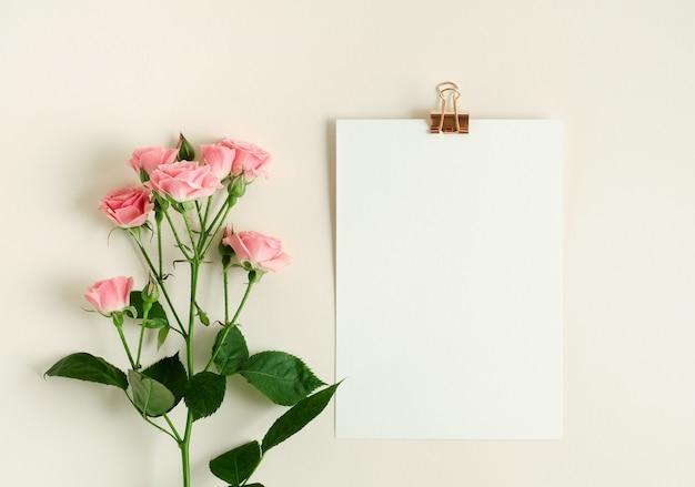 Notizbuchmodell und rosa rosen auf beigem hintergrund. draufsichtfoto