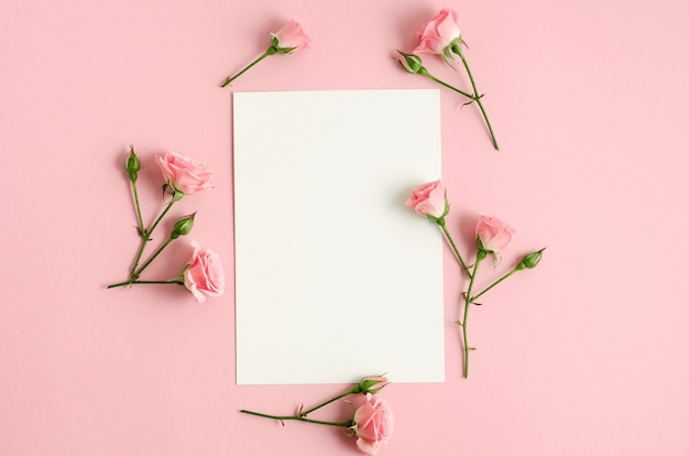 Notizbuchmodell und rosa rosen auf rosa hintergrund. draufsichtfoto