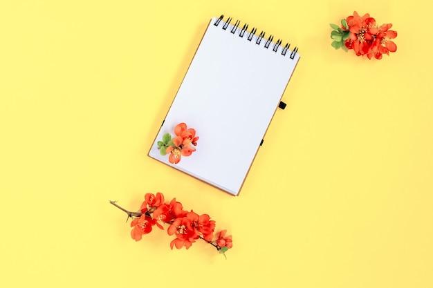 Notizbuchseite mit roten chaenomeles japonica oder quittenblüten auf gelbem hintergrund, draufsicht, flache lage, mockup.