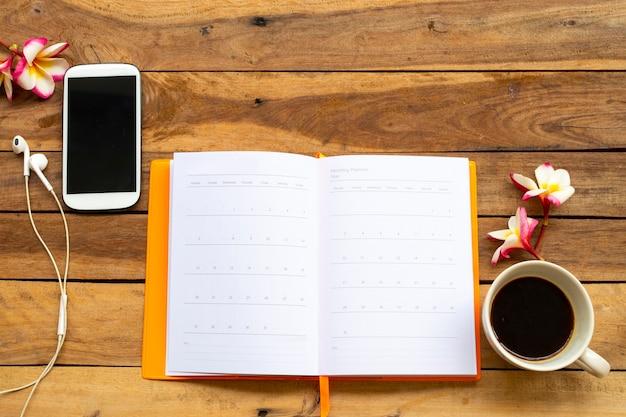 Notizbuchtagebuch, handy und heißer kaffee für geschäftliche arbeiten