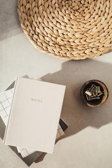 Notizbücher, clips in holzschale, stroh stehen auf beigem beton