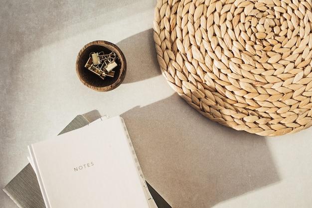 Notizbücher, clips in holzschale, strohhalm auf beiger betonoberfläche