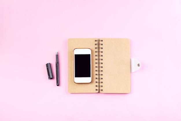 Notizbücher machen, stift und intelligentes telefon auf einem pastellrosahintergrund in handarbeit
