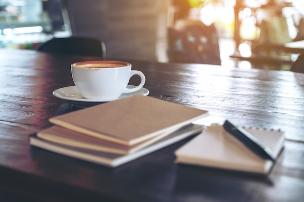 Notizbücher, stift und kaffeetasse auf holztisch im café