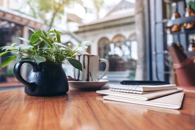 Notizbücher, stift und kaffeetasse auf holztisch