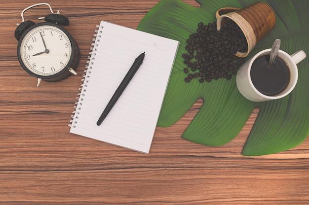 Notizbücher und kaffeetassen auf dem schreibtisch