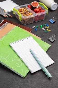 Notizbücher und stift mit schulbox mit früchten und nüssen