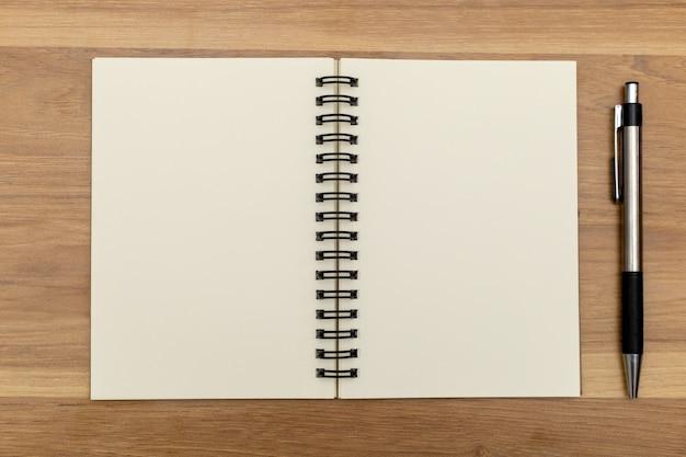 Notizbücher und stifte werden auf den tisch gelegt.