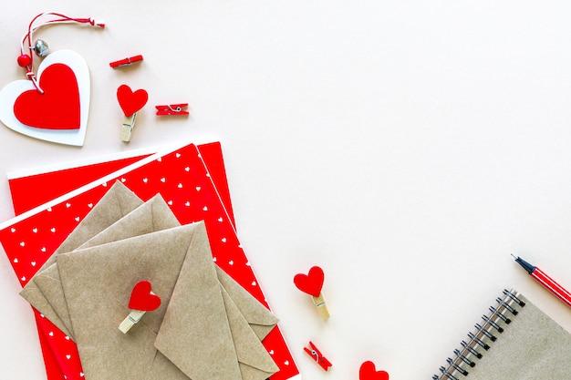 Notizbücher und umschläge für schule oder büro in rot auf einem weißen tisch mit kopierraum.