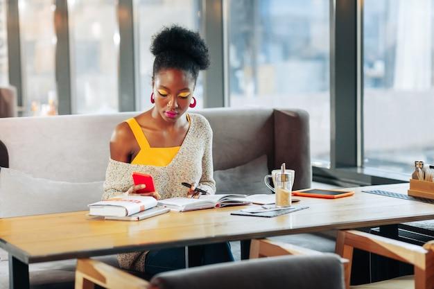 Notizen machen afroamerikanischer internationaler student, der sich während des studiums notizen macht
