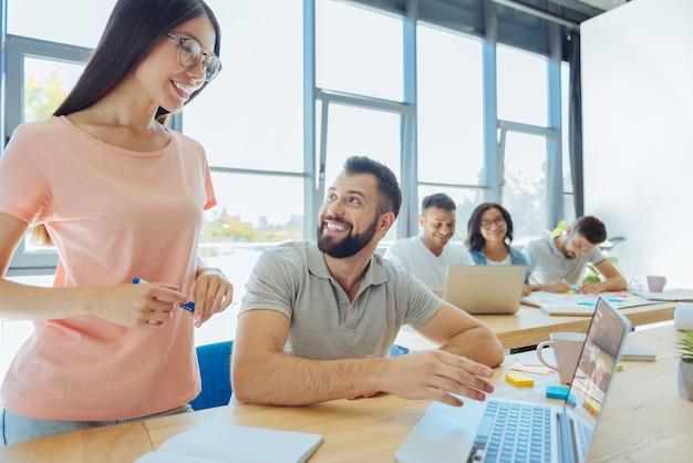 Notizen machen. erfreute positive intelligente frau, die einen textmarker hält und bereit ist zu schreiben, während sie auf den laptopbildschirm schaut