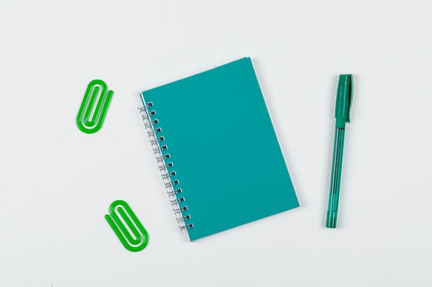 Notizkonzept mit notizbuch, stift, büroklammern auf draufsicht des weißen hintergrunds. horizontales bild