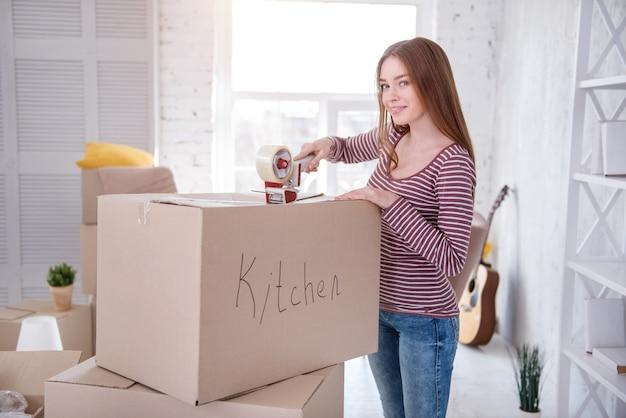 Notwendige utensilien. hübsche junge frau, die für die kamera aufwirft, während küchenutensilien verpackt und die schachtel mit klebeband schließt