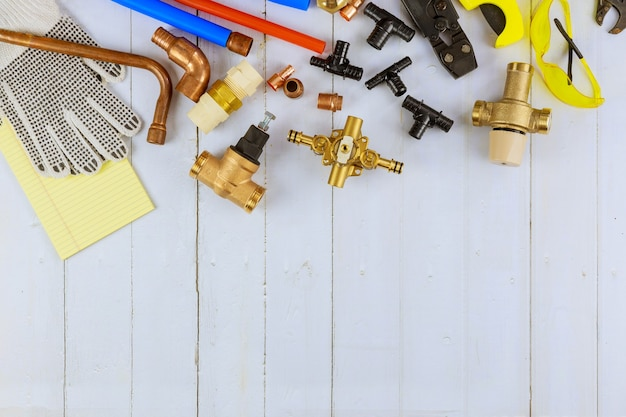 Notwendige werkzeuge für klempner wurden vom handwerker vorbereitet, bevor sanitärmaterialien wie kupferrohr, winkelstück, schraubenschlüsselschlüssel aus rostfreiem stahl auf weißem holzhintergrund repariert wurden