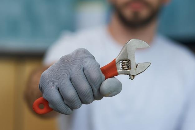 Notwendiges handwerkzeug nahaufnahme der hand eines jungen mechanikers, der einen verstellbaren schraubenschlüssel hält