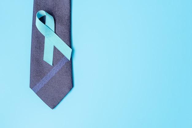 November prostatakrebs-bewusstseinsmonat, hellblaues band mit krawatte auf blauem hintergrund für die unterstützung von lebenden und kranken menschen. men healthcare, internationales konzept für männer und weltkrebstag