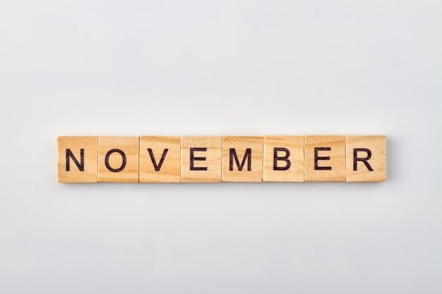Novemberwort geschrieben auf holzklötzen. auf weißem hintergrund isoliert.