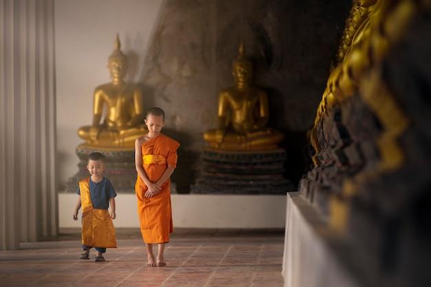 Novizen und assistenten gehen friedlich in einem tempel mit vielen goldenen buddhastatuen.