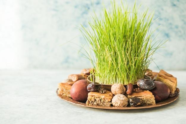 Novruz traditionelles tablett mit grünem weizengrassamen oder sabzi, süßigkeiten und trockenfrüchten pakhlava auf weißem hintergrund. frühlingsäquinoktium, aserbaidschan kopierraum