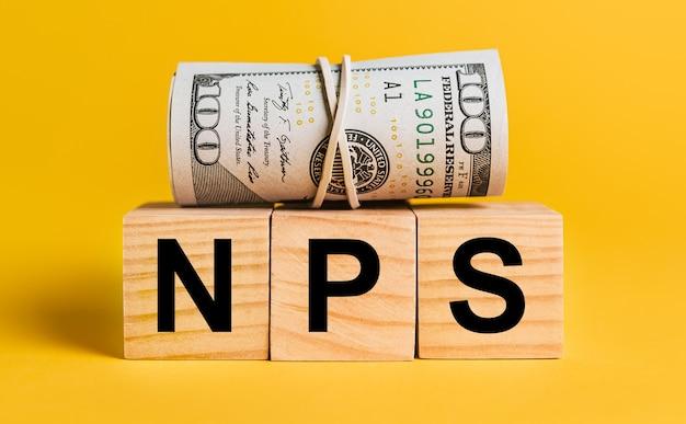 Nps mit geld auf gelbem grund. das konzept von geschäft, finanzen, kredit, einkommen, ersparnissen, investitionen, austausch, steuern