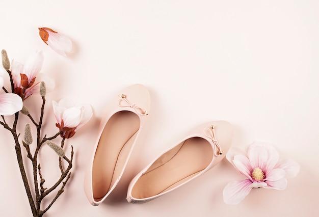 Nude farbige ballerinaschuhe und magnolienblumen.