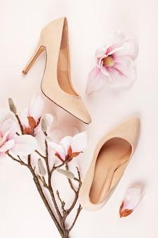 Nude farbige schuhe mit hohen absätzen und magnolienblumen