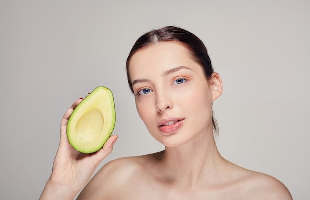 Nude perfekte haut dame mit avocado in der rechten hand