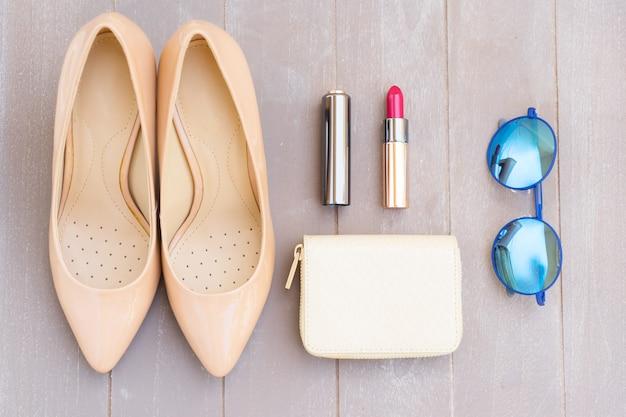 Nudefarbenes high heels stillleben mit portemonnaie, sonnenbrille und rotem lippenstift, draufsicht