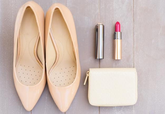 Nudefarbenes high heels stillleben mit portemonnaie und rotem lippenstift, draufsicht