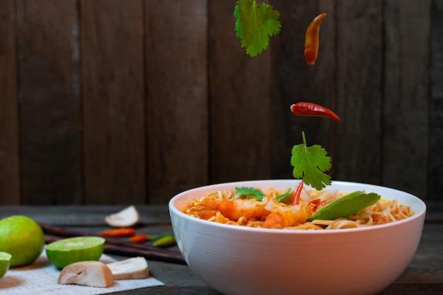 Nudel in würziger suppe mit garnelen und pilz in weißer schüssel auf holztisch.