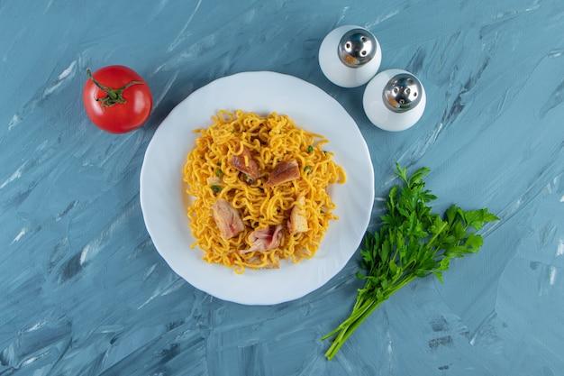 Nudel mit fleisch auf einem teller neben petersilienbündel, tomaten und salz, auf dem marmorhintergrund.