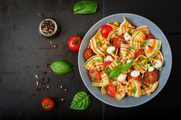 Nudelfarbener farfalle-salat mit tomaten, mozzarella und basilikum.