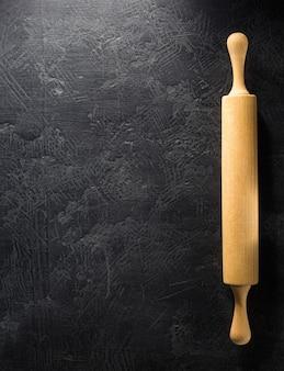 Nudelholz bei schwarzer hintergrundbeschaffenheit