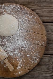 Nudelholz mit pizzateig und mehl auf rollbrett