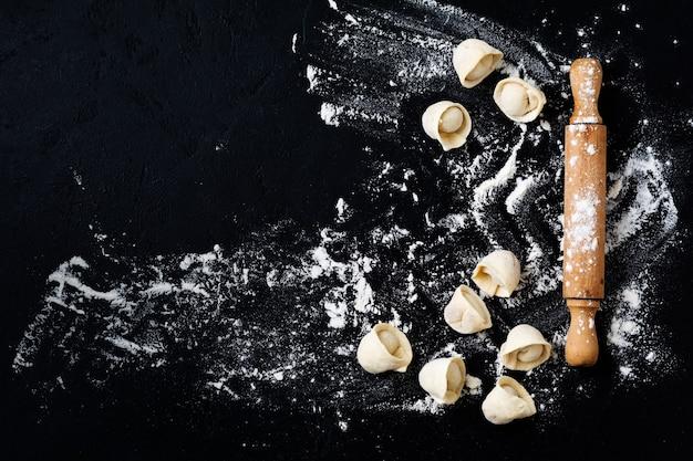 Nudelholz und rohe knödel mit mehl auf dunkelschwarzem backhintergrund, draufsicht, kopienraum für text, menü, rezept. flach liegen.