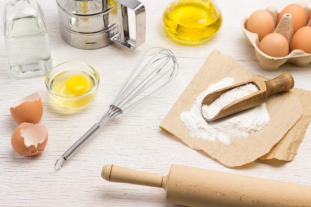 Nudelholz und schneebesen. mit mehl auf papier schaufeln. hühnerschalen und eier im behälter. wasser in der flasche. weißer hintergrund. ansicht von oben