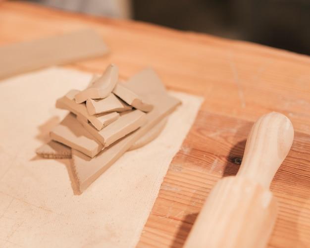 Nudelholz und stapel nasser lehm in der unterschiedlichen form auf hölzernem schreibtisch