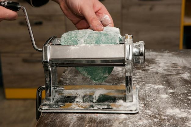 Nudelmaschine auf holztisch mit grünem teig und mehl