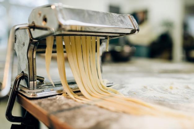 Nudelmaschine mit teig auf hölzernem küchentisch mit mehl nahaufnahme bestreut. traditionelle italienische küche