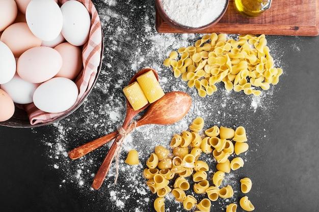 Nudeln auf dem mehl mit eiern herum.