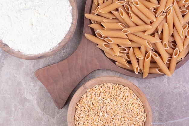 Nudeln auf einer holzplatte mit weizen und mehl in holzbechern.