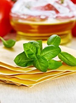 Nudeln für lasagne und basilikum auf hölzernem hintergrund