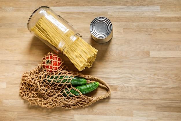 Nudeln, gurken, tomaten und dose mit bohnen auf einem holztisch