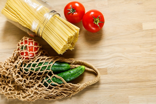 Nudeln, gurken und tomaten mit netzbeutel auf einem holztisch
