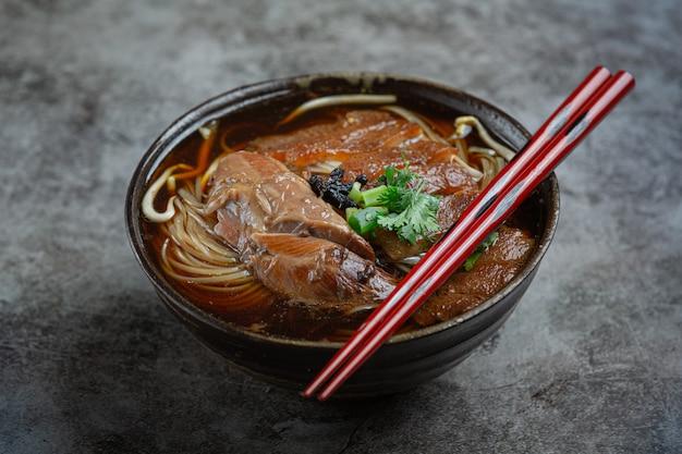 Nudeln in chinesischem schweinefleisch geschmortem schweinefleischeintopf schöne beilagen, thailändisches essen.