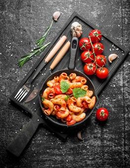 Nudeln in der pfanne auf einem schneidebrett mit tomaten und rosmarin. auf schwarzem rustikalem hintergrund